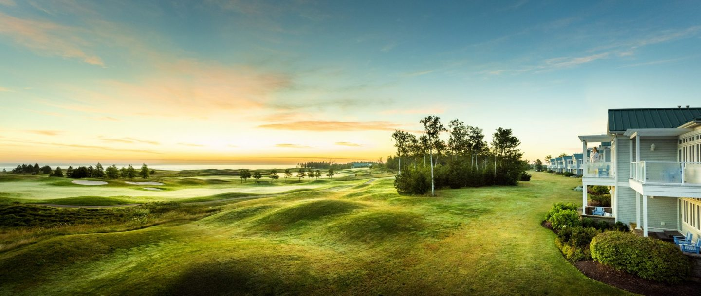 rolling greens of a golf course in front of a villa