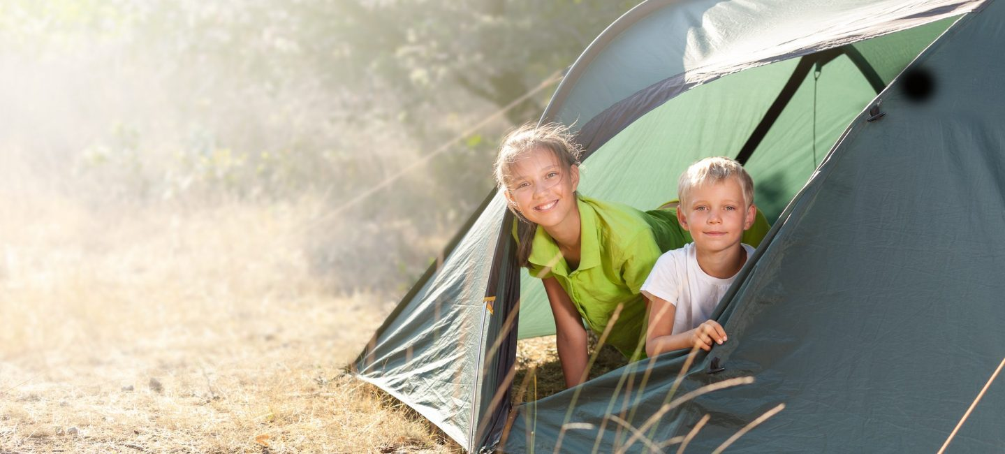 a boy and girl pop their heads out of a green camping tent