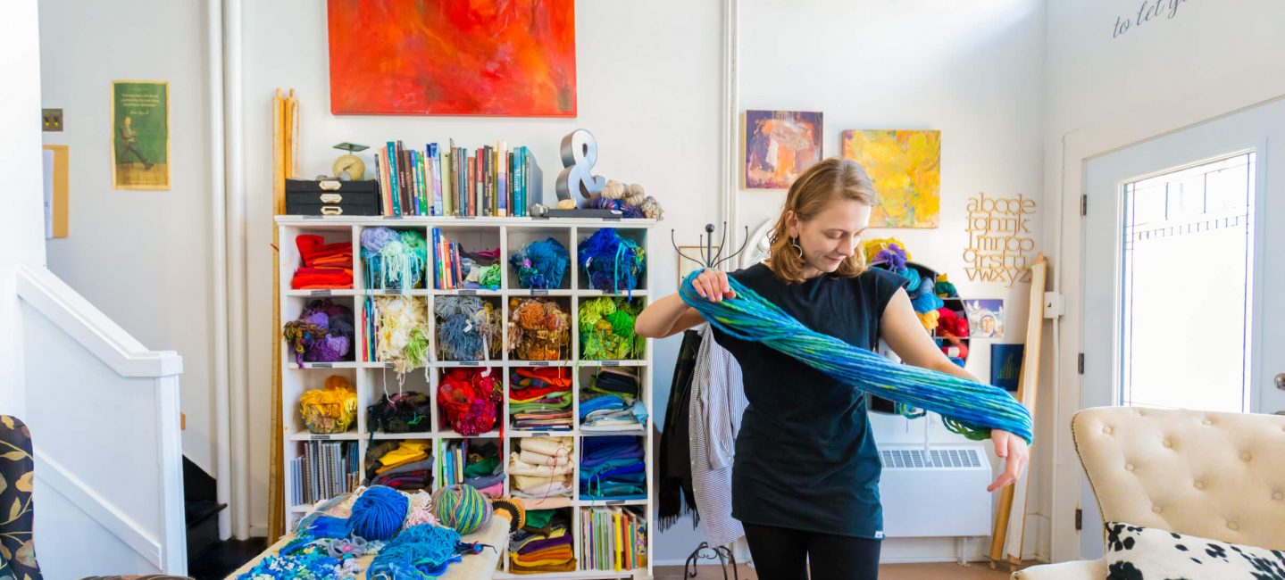 woman holds brightly colored yard in a studio