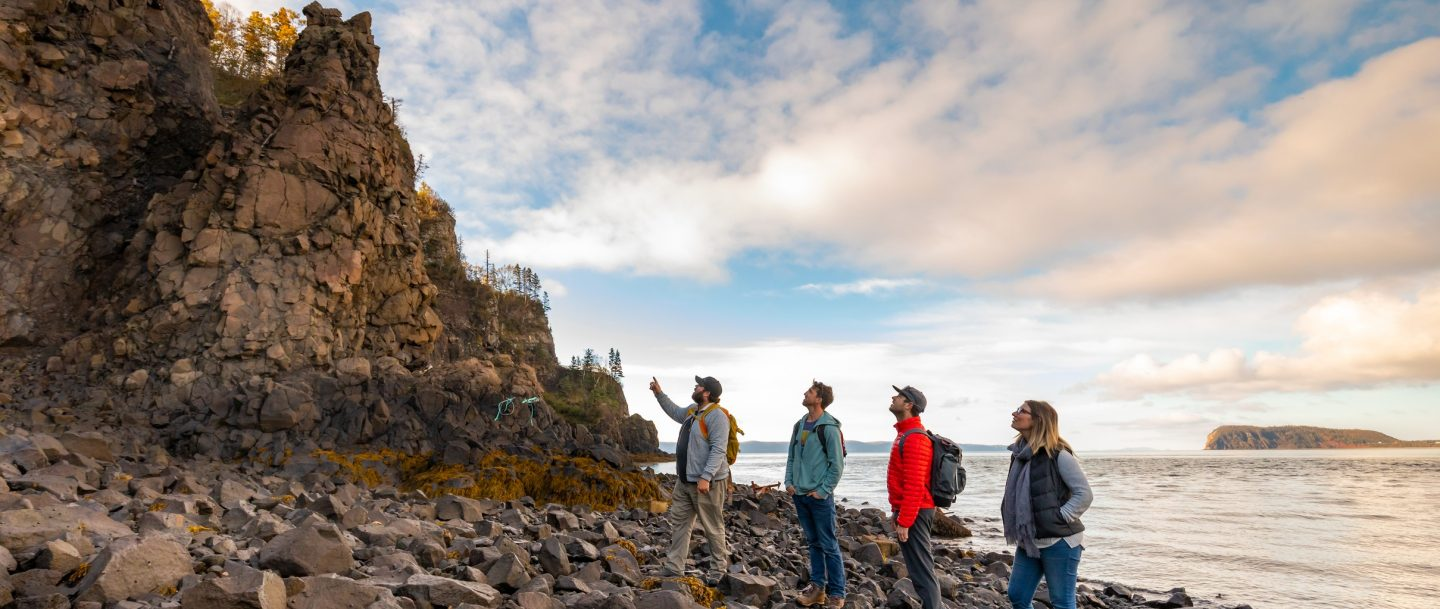 4 people standing on rocky beach staring up at large cliff above